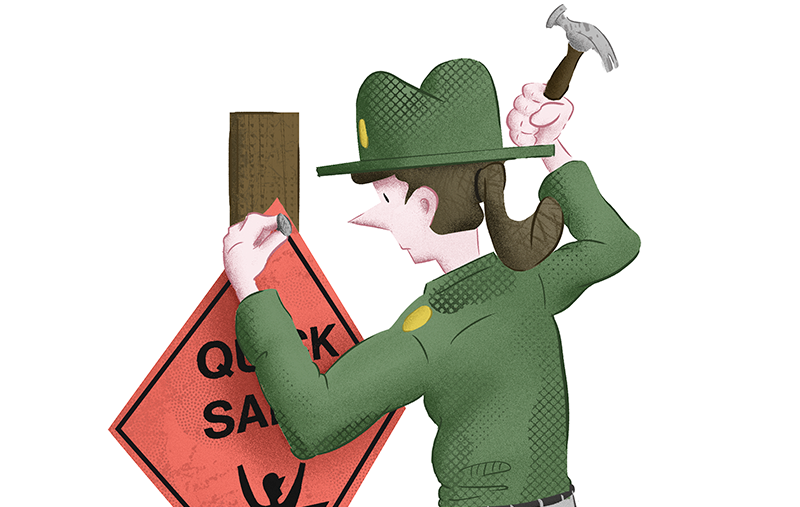 Female park ranger nailing an orange quicksand sign to a post